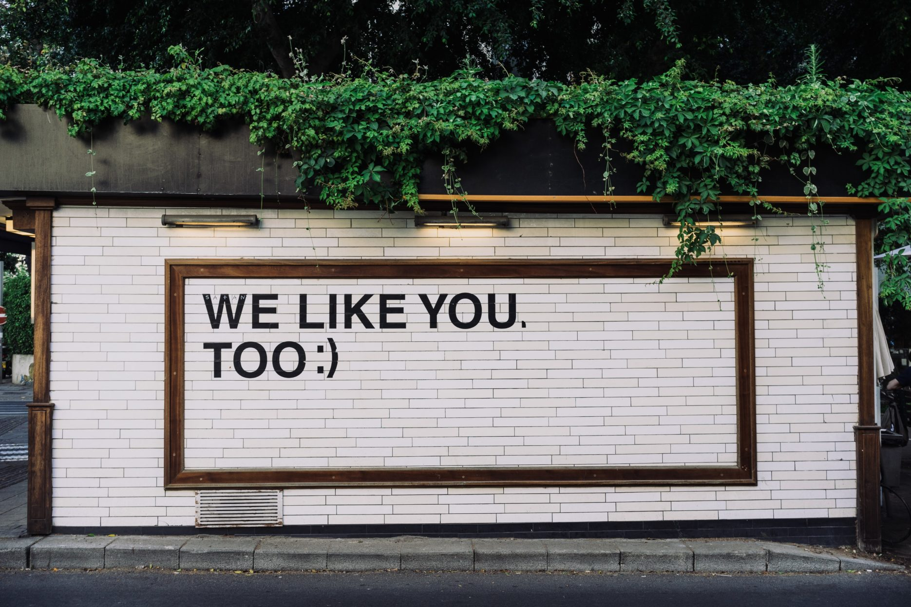 """We Like You Too :)"" in black text on a white brick wall."