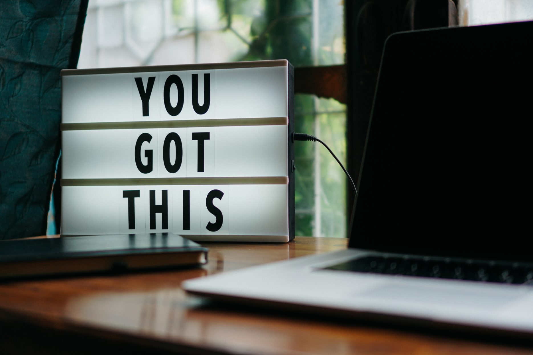 "Lighted sign reads, ""You Got This,"" placed on a desk to the left of an open laptop."