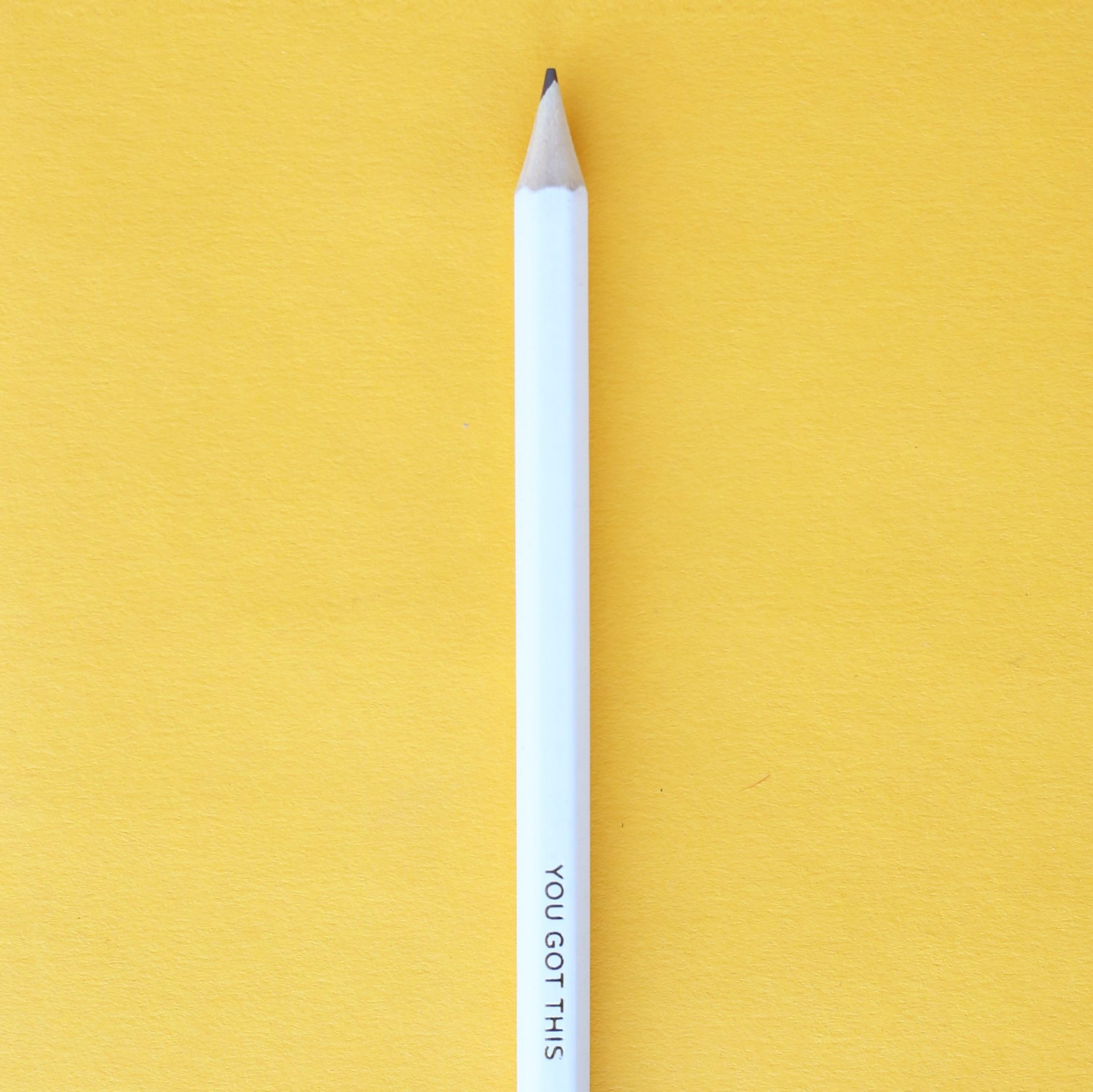 "White pencil on yellow background, pencil reads, ""You Got This!"""