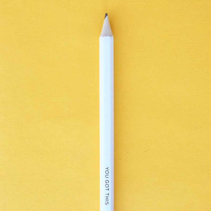 """White pencil on yellow background, pencil reads, """"You Got This!"""""""
